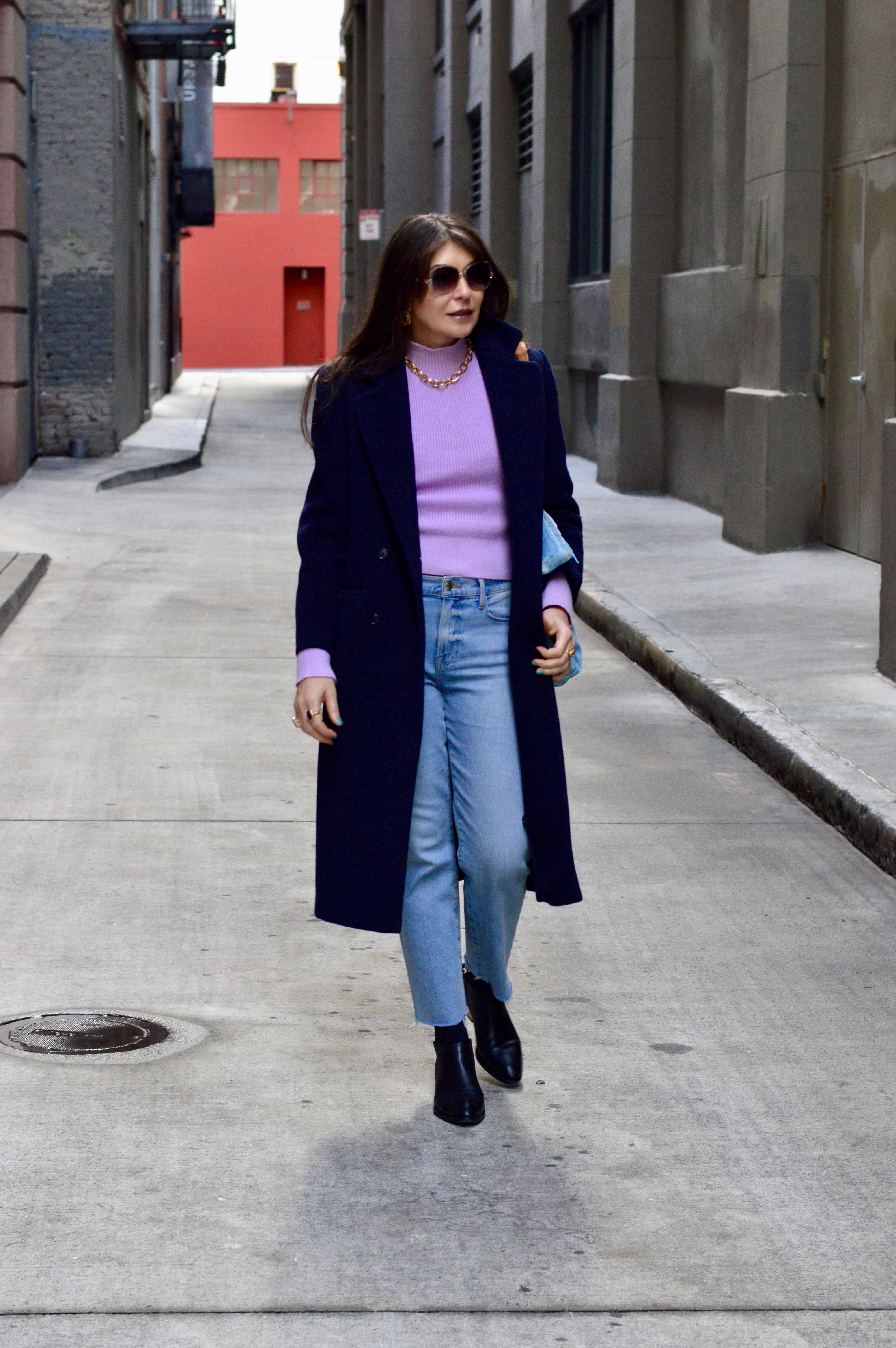 Lilac sweater and light wash jeans.